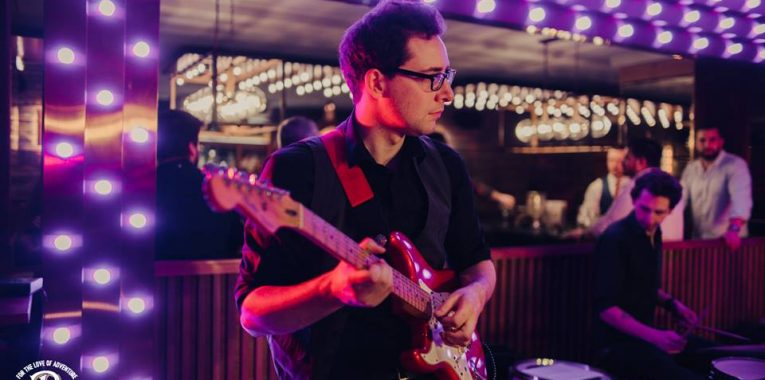 man playing guitar at venue with bright purple mood lights